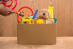 caixa-guardando-voluntária-da-doação-do-homem-com-brinquedos-velhos-90351052